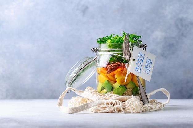 Salada caseira em frasco de vidro com quinoa e legumes com etiqueta hora do almoço sem plástico e tirar o conceito