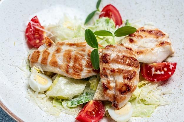 Salada césar com filé de peito de frango grelhado e queijo parmesão. fundo de receita de comida. fechar-se.
