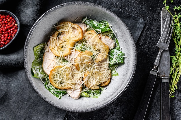 Salada césar com queijo parmesão, biscoitos costa. comida saudável. fundo preto. vista do topo.