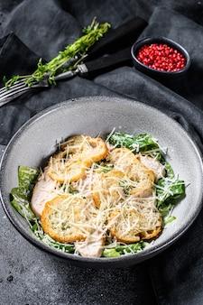Salada césar com queijo parmesão, biscoitos costa. comida saudável. fundo preto.