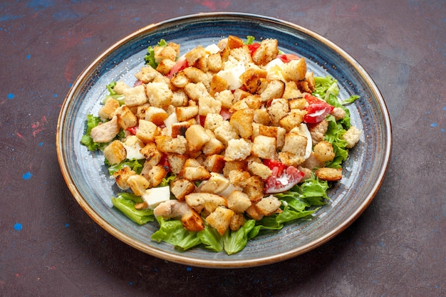 Salada césar de vista frontal com vegetais fatiados e biscoitos em superfície escura