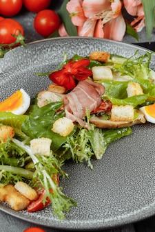 Salada césar em prato cinza com decoração