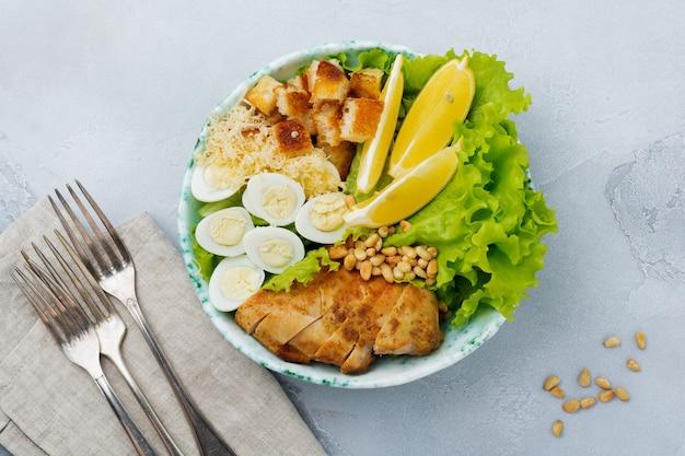 Salada césar tradicional com ovos de codorna e pinhões em uma tigela de cerâmica clara sobre uma pedra cinza ou fundo de concreto.