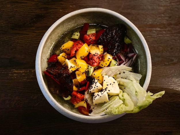 Salada choban de pepinos, tomates, pimentões e queijo em um prato branco em uma madeira isolada