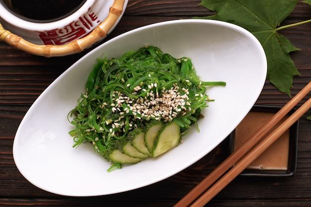 Salada chuka com pepinos, sementes de gergelim e molho, em um prato branco, com um bule de chá japonês, pauzinhos e folhas de bordo, sobre um fundo de madeira