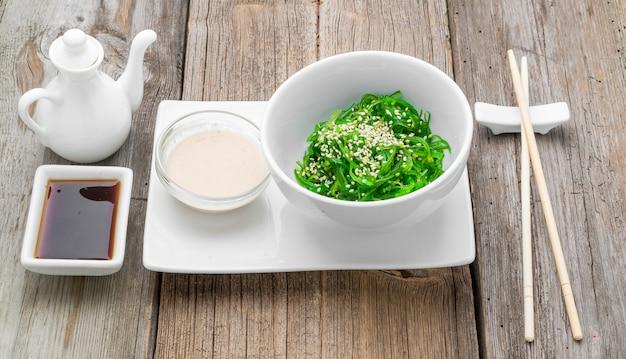 Salada chuka e close-up de gengibre em conserva em cima da mesa.
