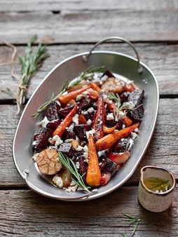 Salada com alecrim de cenouras de beterraba assada e alho em um fundo de madeira