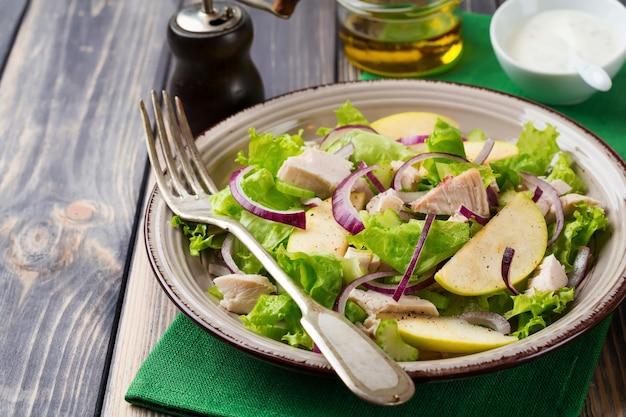 Salada com alface, maçã, aipo, cebola e frango na placa cinza no fundo escuro de madeira. foco seletivo.
