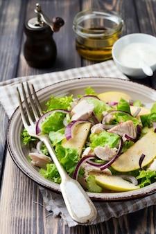 Salada com alface, maçã, aipo, cebola e frango no prato cinza