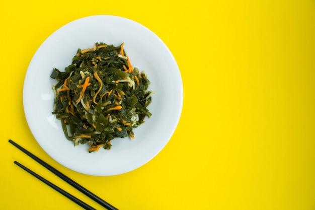 Salada com algas, aipo e cenoura no prato branco. vista superior. copie o espaço.