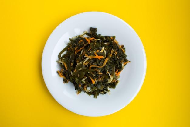 Salada com algas, aipo e cenoura no prato branco. vista superior.
