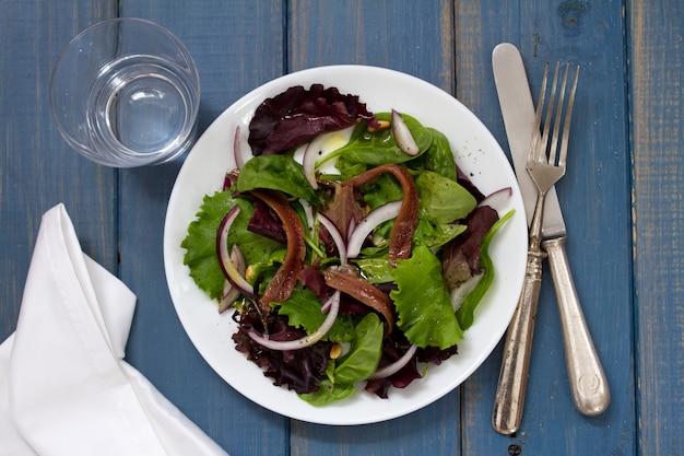 Salada com anchovas e cebola na chapa branca na superfície azul e copo de água