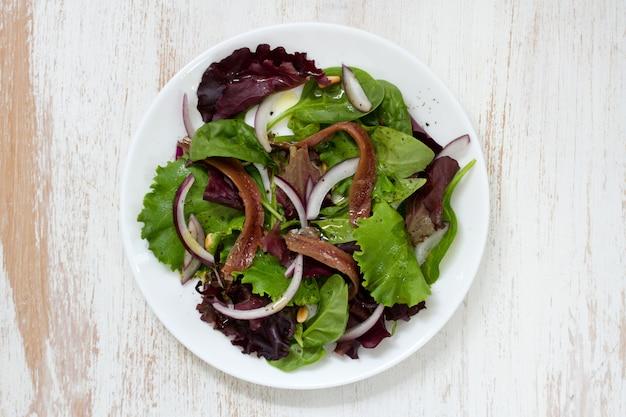 Salada com anchovas e cebola na chapa branca na superfície branca