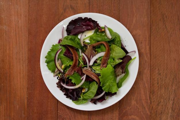 Salada com anchovas e cebola na chapa branca na superfície marrom