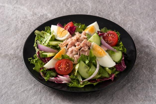 Salada com atum, ovo e legumes na chapa preta e superfície cinza