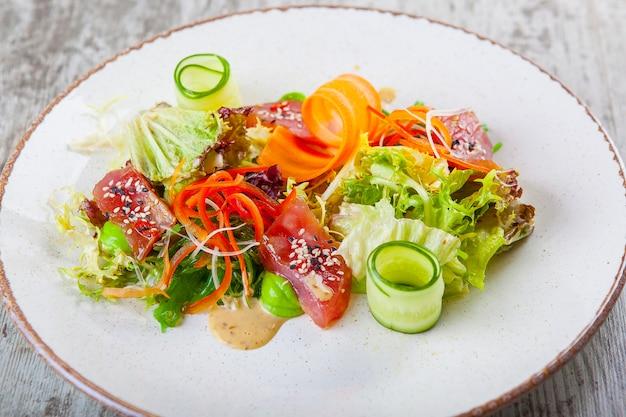Salada com atum pepinos cenouras pimentões e molho