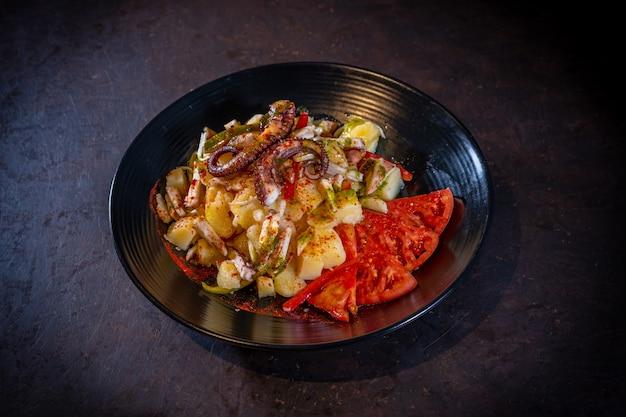 Salada com batatas e polvo com páprica picante em um fundo preto, em uma placa preta