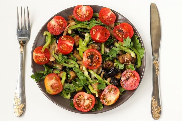 Salada com beringelas e tomate cereja em um prato escuro em um branco