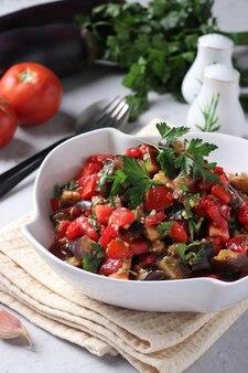 Salada com berinjela, tomate, alho e salsa em uma tigela branca sobre fundo cinza claro. formato vertical