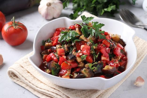 Salada com berinjela, tomate, alho e salsa em uma tigela branca sobre um fundo claro. fechar-se