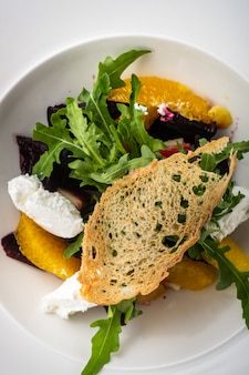 Salada com beterraba seca, maçã, laranja e queijo de cabra macio.