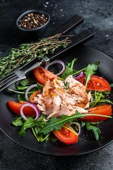 Salada com bife de filé de salmão assado, rúcula fresca e tomate em um prato.