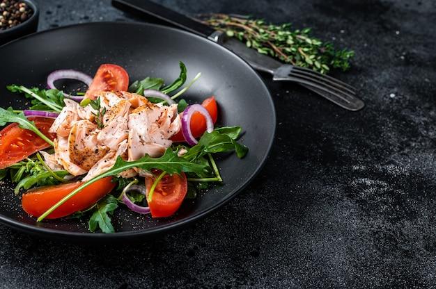 Salada com bife de filé de salmão assado, salada fresca de rúcula e tomate em um prato. fundo preto. vista do topo. copie o espaço.