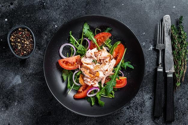 Salada com bife de filé de salmão assado, salada fresca de rúcula e tomate em um prato. fundo preto. vista do topo.