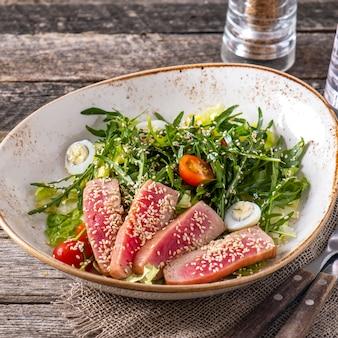 Salada com bife fatiado de atum no gergelim, rúcula, tomate e ovos de codorna