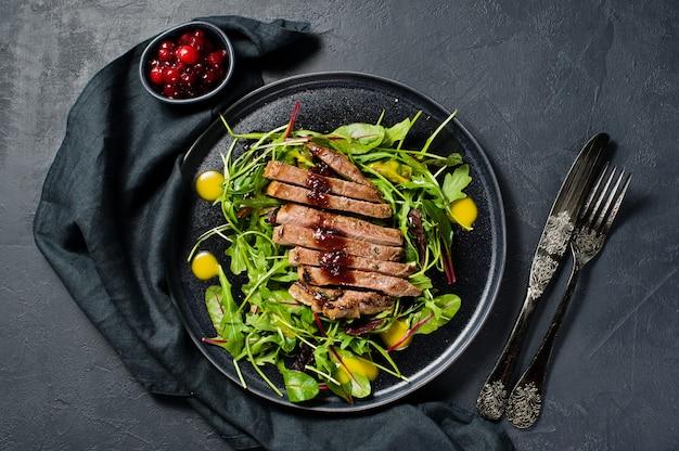 Salada com bife, rúcula e acelga em uma placa preta.