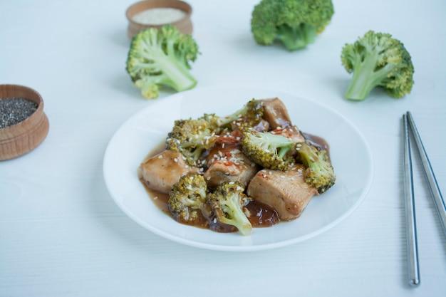 Salada com brócolis e frango. salada quente ao molho servido em um prato branco. prato de estilo asiático. luz .
