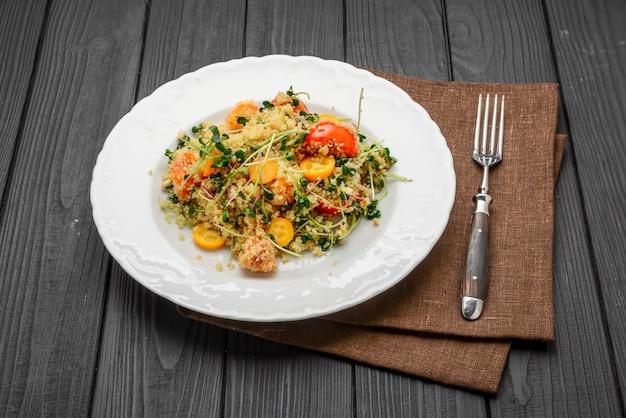 Salada com bulgur e legumes, tabule, em madeira escura. tingimento.