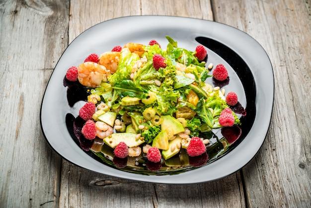 Salada com camarão, abacate e framboesas frescas, em um prato preto.