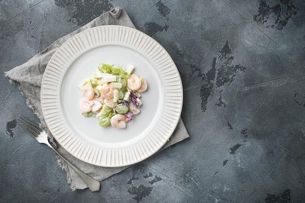 Salada com camarão, abacate, tomate e maionese no conjunto de alface, com molho de maçã e uva, na mesa cinza, vista de cima plana lay