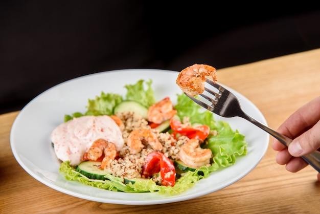 Salada com camarão, quinua, tomate, pimentão, pepino, alface, maionese em prato redondo branco na mesa de madeira