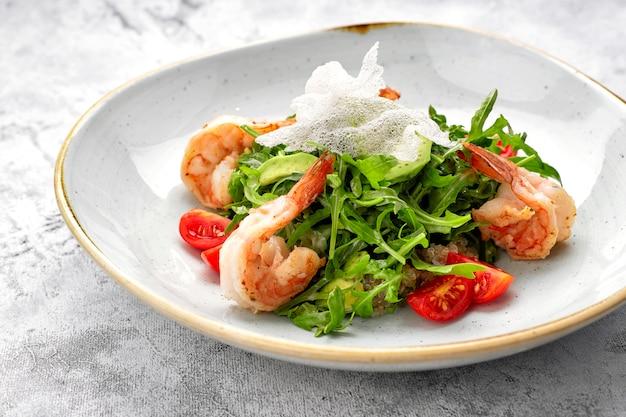 Salada com camarão, tomate e rúcula, num prato branco, sobre fundo claro