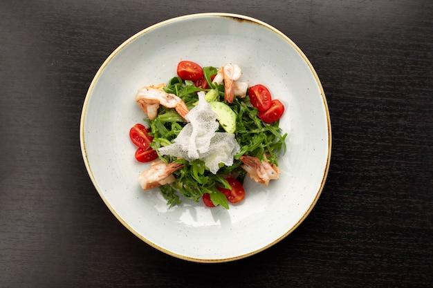 Salada com camarão, tomate e rúcula, num prato branco, sobre fundo escuro