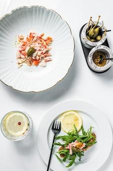 Salada com carne de caranguejo na mesa da cozinha. fundo branco. vista do topo.
