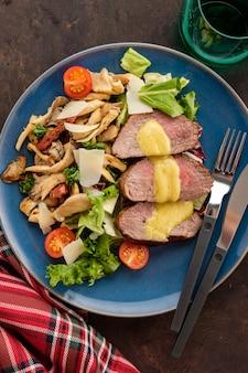 Salada com carne quente com cogumelos ostra, tomate e verduras. vista do topo