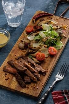 Salada com carne quente com cogumelos ostra, tomate e verduras.