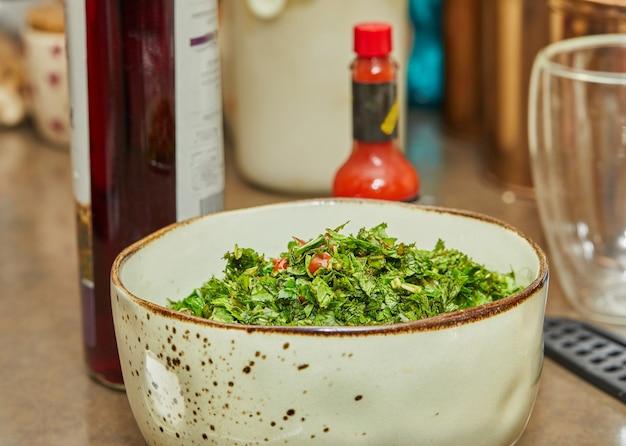 Salada com cebolinha, tomate e manjericão misturado em uma tigela funda.