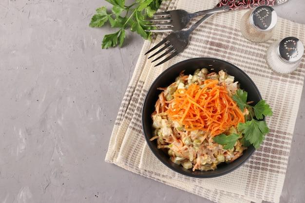Salada com cenoura coreana, carne e ervilhas em uma tigela escura