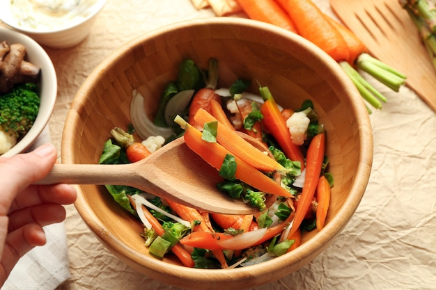 Salada com cenoura em uma tigela de madeira closeup