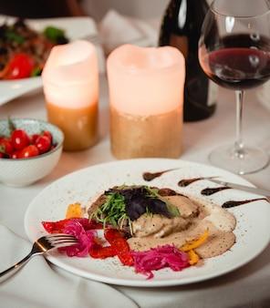 Salada com ervas e molho cremoso com um copo de vinho tinto.
