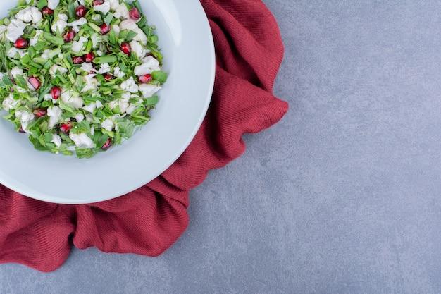 Salada com ervas, frutas e vegetais em uma travessa