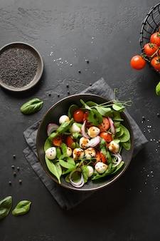 Salada com espinafre, legumes de verão e mussarela em fundo preto. vista do topo.