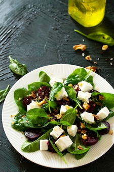 Salada com espinafre, queijo feta, beterraba e molho de óleo vegetal de nozes espaço livre para o seu texto