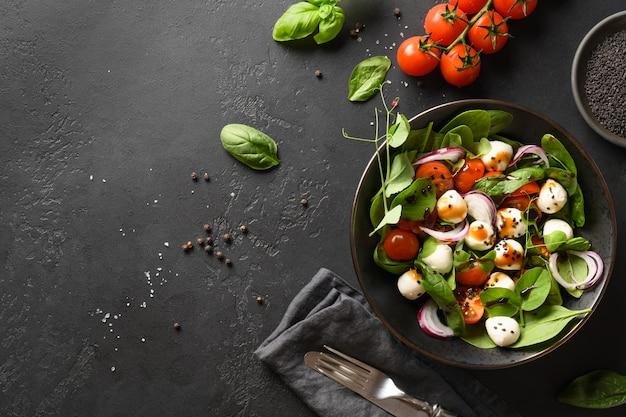 Salada com espinafre, tomate cereja, cebola e mussarela em fundo de pedra preto. vista do topo.
