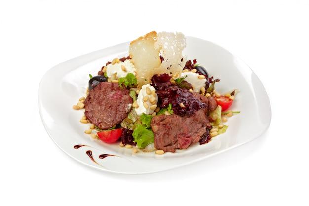 Salada com fatias de carne grelhada e alface isolada no branco