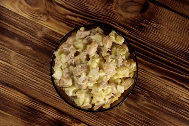Salada com feijão branco, batata, carne de frango, ovos e maionese na mesa de madeira. vista do topo